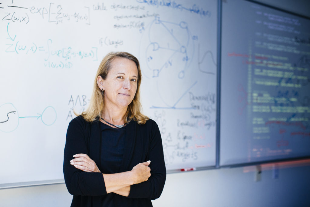 Computer Science Professor Lise Getoor stands with arms folded in front of a white board